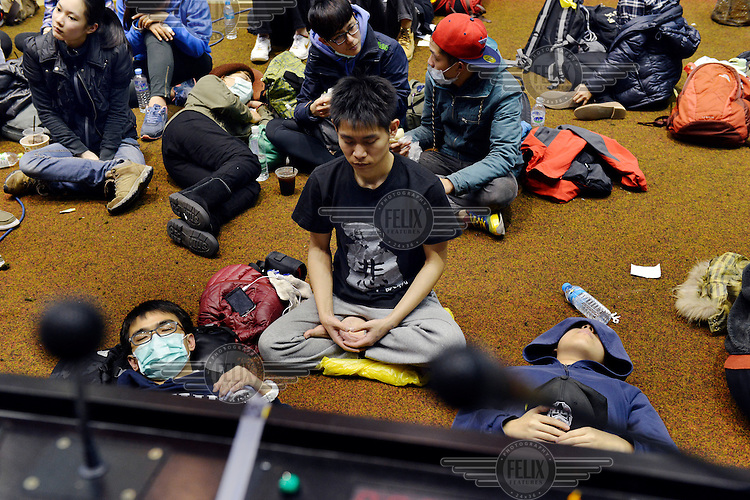 """A young student meditates amongst a group of students inside Taiwan's Legislative Yuan (Parliament) Building on their 4th day of occupation in opposition to the passing of the Cross-Straight Service and Trade Agreement between Taiwan and China. The students, and many normal Taiwanese, fear the erosion of their hard-won democracy and, eventually, independence, making them, in the words of one student protestor 'no better off than Hong Kong'. Ma ying-jeoh bears the brunt of the protestors ire; known as """"Ma 9%"""" after his latest approval rating, he is seen as kowtowing to the demands of China and selling out Taiwan."""