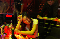 Armani Club.  Liu lin Road area. This scene is a mix of young folks, mistresses, and male and female prostitutes. Woman dancing with concerned look seems to me to be entering this society at some level and uncomfortable about it... maybe she is from the countryside... Many of the girls from the countryside come to the city and sell themselves to pay for their brothers education. The girl in sunglasses had line-ups of male prostitutes at her table for her to choose.