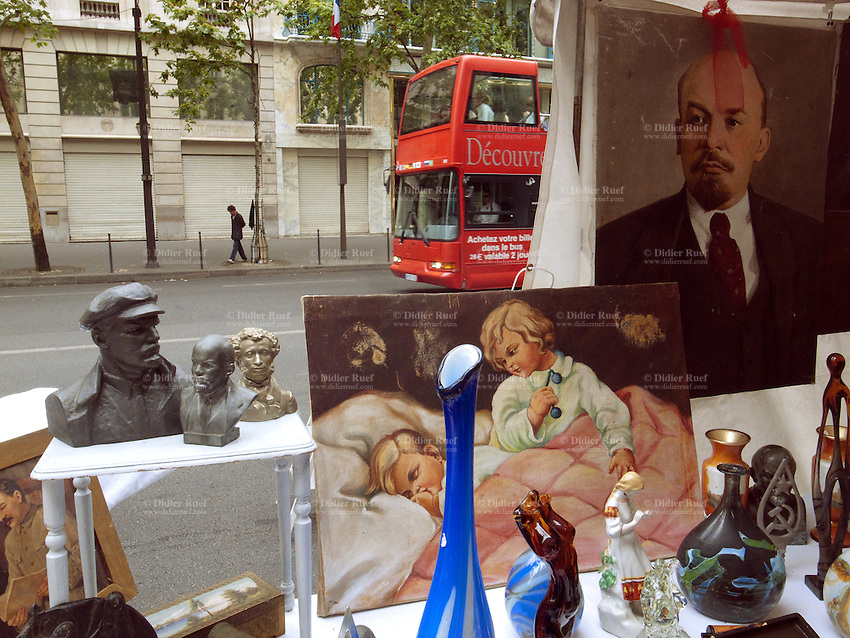 France. Paris. Flea market on Sunday morning on Boulevard des Capucines. Various objects for sale. An old painting with Lenin. A double decker bus for tourists is riding on the road. Vladimir Ilyich Lenin (1870- 1924) was a Russian Marxist revolutionary and communist politician who led the October Revolution of 1917. As leader of the Bolsheviks, he headed the Soviet state during its initial years (1917-1924), as it fought to establish control of Russia in the Russian Civil War and worked to create a socialist economic system. As a politician, Lenin was a persuasive orator, as a political scientist his extensive theoretic and philosophical developments of Marxism produced Marxism Leninism, the pragmatic Russian application of Marxism. 10.07.2011 © 2011 Didier Ruef