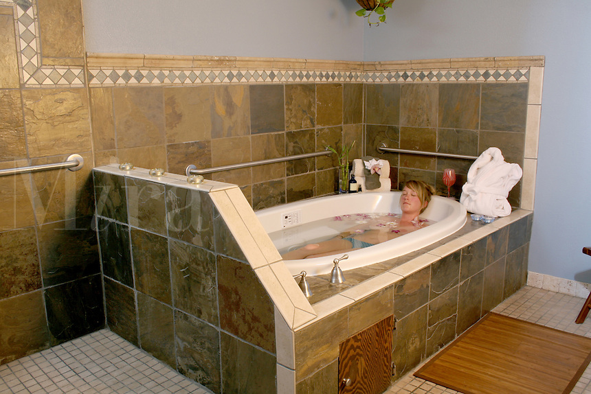 Released health spa woman relaxing in warm tub water