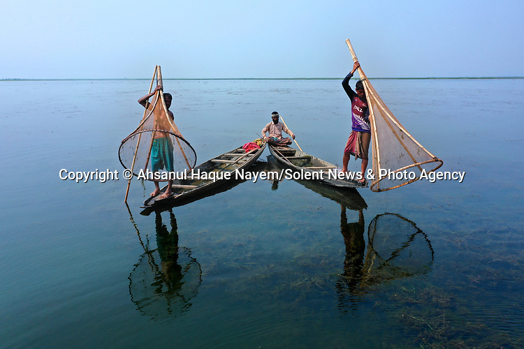 Reflections of fishermen ripple on the surface of a lake as the men use traditional techniques to catch the fish.  The fishermen stand at the end of wooden canoes with large bamboo sticks and nets in their hands, the tools of the trade in this region of Bangladesh.<br /> <br /> They are fishing in the Tanguar Haor, a vast area of wetlands including lakes and swamps in the region of Sunamganj.  SEE OUR COPY FOR DETAILS.<br /> <br /> Please byline: Ahsanul Haque Nayem/Solent News<br /> <br /> © Ahsanul Haque Nayem/Solent News & Photo Agency<br /> UK +44 (0) 2380 458800