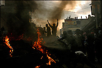 Anti-monarchy protesters cheer after setting a car on fire and blocking the road in Kathmandu, Nepal on 20 April, 2004. Weeks of clashes between police and protesters calling on the king to reinstate democracy lead to thousands of arrests and hundreds injured.<br />