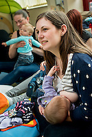 """A mother breastfeeding her baby at a drop-in breastfeeding support centre while talking to another mother.<br /> <br /> Image from the """"We Do It In Public"""" documentary photography project collection: <br />  www.breastfeedinginpublic.co.uk<br /> <br /> Dorset, England, UK<br /> 17/04/2013"""