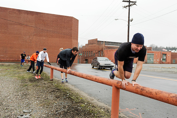 December 22, 2014. Lexington, North Carolina.<br /> Mayor Newell Clark, right, leads his exercise group on a rail climb and jump as part of their workout routine incorporating local infrastructure.<br />   Newell Clark, the 43 year old mayor of Lexington, NC, leads a group of friends and colleagues on a 4 times a week exercise routine around downtown. The group uses existing infrastructure, such as an abandoned furniture factory, loading docks, stairs, and handrails to get fit and increase awareness of healthy lifestyles in a town more known for BBQ.<br /> Jeremy M. Lange for the Wall Street Journal<br /> Workout_Clark