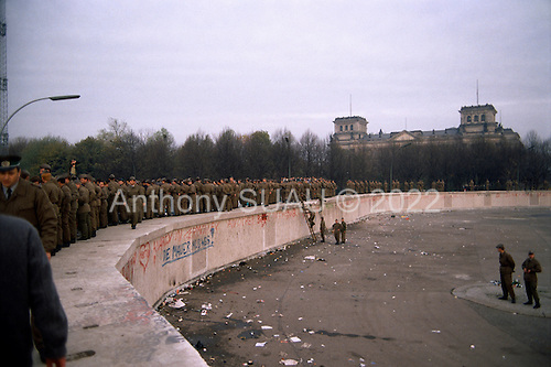 East Berlin, East Germany<br /> November 11, 1989<br /> <br /> East German police climb onto the Berlin Wall at the  Brandenburg Gate. The East German government lifts travel and emigration restrictions to the West on November 9, 1989.
