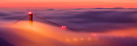 A fine art landscape panorama of the Golden Gate Bridge with one of its arches emerging through a dense fog bank at sunrise, with dawn colors of red, gold and mauve filling the sky and coloring the fog.  The light at the top of the bridge's arch shines, and a few car headlights are faintly visible through the fog.
