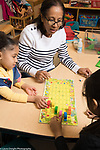 Education Preschool 4 year olds female teacher working with two girls on playing board game with die and rules