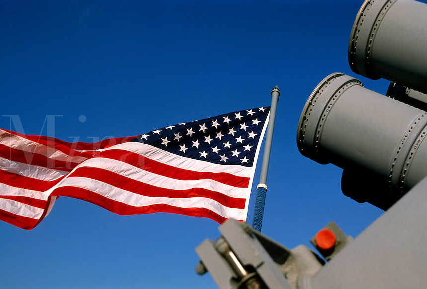 An American flag ripples in the breeze aboard a naval vessel.