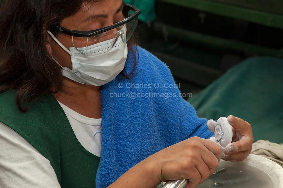 Antigua, Guatemala.  Jade Factory Workshop.  Woman Carving a Design into a Piece of Jade.