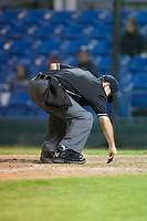 Home plate umpire Phil Bando cleans off home plate during the Pioneer League game between the Helena Brewers and the Great Falls Voyagers at Centene Stadium on August 19, 2017 in Helena, Montana.  The Voyagers defeated the Brewers 8-7.  (Brian Westerholt/Four Seam Images)