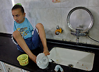 """Gaza.June.09.2008.Aya Masouad 8 years born without arms,use here toes and feet to go around with her daily life,she cleaning dishes after she eats. she easts or drink with her toes , she love her life and thanking God, she practice her life as she is normel people . """" Photo by Fady Adwan/propaimages"""""""