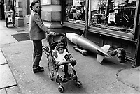 USA. New York City. A blak mother and her child in a stroller walk on Broadway Avenue and passes by a shop selling a bomb on the street. African Americans, also referred to as Black Americans or Afro-Americans, are citizens or residents of the United States. © 1985 Didier Ruef