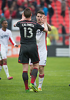 Toronto, Ontario - May 3, 2014: Toronto FC defender Steven Caldwell #13 and New England Revolution forward Patrick Mullins #7 give each there a high five at the end of a game between the New England Revolution and Toronto FC at BMO Field.<br /> The New England Revolution won 2-1.