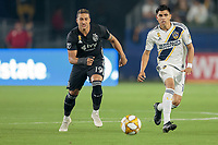 CARSON, CA - SEPTEMBER 15: Joe Corona #14 of the Los Angeles Galaxy and Erik Hurtado #19 of Sporting Kansas City battle for a loose ball during a game between Sporting Kansas City and Los Angeles Galaxy at Dignity Health Sports Complex on September 15, 2019 in Carson, California.