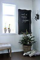 In the entrance hall is a blackboard, ordinarily used for messages, underneath is a small Christmas tree, already sheltering some Christmas goodies