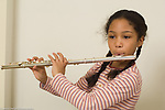 10 year old girl playing musical instrument flute at home