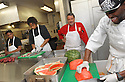 Liberty Kitchen Chef Kevin Hackett (in red)  oversees trainees Charles Williams and Jory Adams with the help of staff cook Paul Dyer as they prepare lunch for students at the New Orleans College Prop School in New Orleans, Thurs., March 22, 2012.