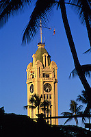 The Aloha Tower in Honolulu, framed by the silhouette of a palm tree