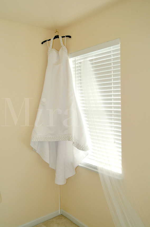 Wedding dress and veil hanging on a hanger in the corner of a room.