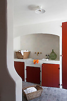 The laundry room has cheerful red-painted cupboard doors and a Belgian tiled floor