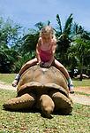 MUS, Mauritius, bei Rivière des Anguilles, La Vanille Crocodile Park & Nature Reserve: Maedchen reitet auf Riesenschildkroete | MUS, Mauritius, near Rivière des Anguilles, La Vanille Crocodile Park & Nature Reserve: girl riding a giant turtle