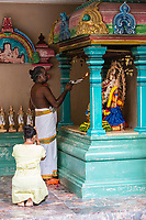 Hindu Priest Praying to Deity for Worshiper, Sri Mahamariamman Hindu Temple, Kuala Lumpur, Malaysia.