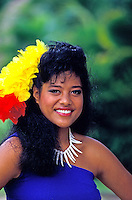 Close-up of a beautiful Samoan dancer wearing a royal blue sarong and bright yellow and red headpiece against a muted green background.