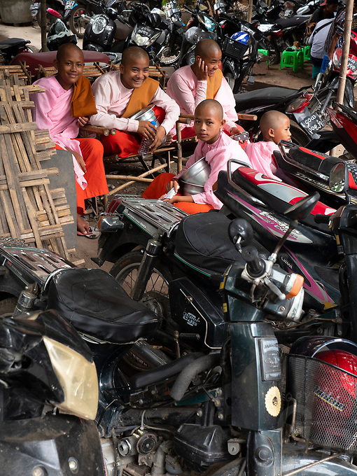 Buddhist Nuns taken a rest after collecting alms, surrounded by thousands of motor bikes and scoots outside the Jade Market in Mandalay, Myanmar, Burma