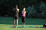 Couple practicing yoga in the park, Milan, Italy,