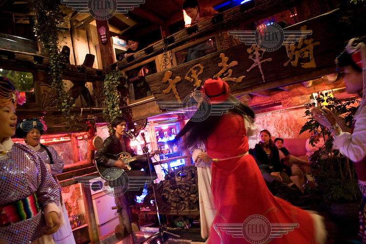 Performers dressed in traditional Nakhi (Naxi) costume encourage tourists to sing songs in a bar in the old city of Lijiang, a centre of Nakhi culture which is a UNESCO World Heritage Site.