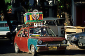 Salvador, Bahia State, Brazil. Very battered old Chrysler car with brightly painted box and bicycle on roof.