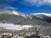 The snow covered Eagle Lake with Franconia Ridge in the background from along Greenleaf Trail in the White Mountains of New Hampshire. The Appalachian Trail travels over this exposed ridge.
