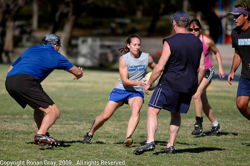 """Saturday, 01/17/09:  San Diego, California, USA:  BA Antlitz, Mandy Wilson, John Schleimer Ruth Oram and XXXXX  play a mixed game of touch rugby at Torrey Highlands Park in Del Mar.  An informal group of players meets every Saturday morning at 11am for games.  The sport of Touch Rugby is a fast paced, exciting version of the full contact game that is gaining popularity in San Diego.  As the name suggests, the """"touch"""" version is not a full contact game.  Players are only allowed to make contact by hand with opposing players while they have possesion of the ball.  Possesion passes to the defending team after a score or if six """"touches""""  have been made while the attacking team moves the ball towards the goal line.  Pick-up games can be found most Saturdays in the Del Mar Park and on Sunday mornings at the beach in Del Mar or Sunday afternoons in South Mission Beach."""