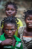 Three children all sporting a distinctive hair style. Doctor Richard Hardi and his medical medical team have come to the remote village of Pania to perform eye surgery. <br /> <br /> From his base in Mbuji Mayi Hungarian ophthalmologist Friar Richard Hardi and his team travelled deep into the Congolese rainforest, by 4x4 and canoe, to treat people in isolated communities most of whom have never seen an ophthalmologist. At a small village called Pania they established a temporary field hospital and over the next three days made hundreds of consultations. Although both conditions are preventable, many of the patients they saw had Glaucoma or River Blindness (onchocerciasis) that had permanently damaged their eyesight. However, patients with cataracts, a clouding of the eye's lens, who were suitable for treatment were booked for an operation. For two days the team carried out the ten minute procedure on one patient after another. The surgery involves making a 2.2mm incision into the remove the damaged lens that is then replaced by an artificial one. Doctor Hardi is one of the few people willing to make such a journey but is inspired to do so by his faith and, as he says: 'Here I feel that I can really make a difference in people's lives'. /Felix Features