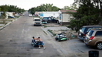 Children play with a toy car in a trailer park in Garden City, Kansas. This is home to many of the migrant workers who have come to the town to work at the Tyson meatpacking plant. The Tyson facility kills and processes between five and six thousand beef cattle every day. Kansas dominates the American beef industry, producing 25% of all beef raised in the USA. However, the industry is heavily dependent on cheap immigrant labour.