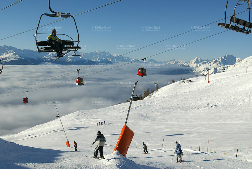 """Switzerland. Valais. Crans Montana. Winter ski resort. CMA ( Crans Montana Aminona) red cable cars and chair lifts are carrying people to the top of the mountain, while other are skiing down  the """"Pas du loup"""" slopes on a sunny day with blue sky. Foam protection on the poles of snow cannons. The fog is covering the Rhone valley. © 2005 Didier Ruef"""