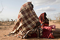 Kenya - Dadaab - 21st July 2011. Refugees who arrived 16 days ago sitting next to their tent isolated from the rest of the camp as they had been threatened by local communities claiming that they were occupying their land.