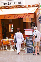 A couple reading the menus outside the restaurant Le Puits, the well. Collioure. Roussillon. France. Europe.
