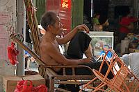 Mature man lying on a bamboo chair and smoking a cigar, Fuli Town Market, Fuli Village, Guangxi, China.