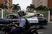 """MEDELLIN - COLOMBIA, 30-03-2020: Un carro funerario porta un cartel con la leyenda. """"Aunque todos tenemos que morir, no nos matemos"""" por las calles de Medellín durante el octavo día de la cuarentena total en el territorio colombiano causada por la pandemia  del Coronavirus, COVID-19. / A funeral car carries a sign with the message: Although we all of have to die, not kill us"""" through the streets of Medellin during the eighth day of total quarantine in Colombian territory caused by the Coronavirus pandemic, COVID-19. Photo: VizzorImage / Leon Monsalve / Cont"""