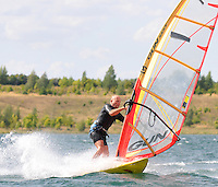 Surfen im Schladitzer See. Erst zum zweiten Mal in dieser Surfsaison erreichte der Wind im Tagesdurchschnitt 5 Beaufort, was einer Geschwindigkeit von 29 bis 38 km/h entspricht. Je mehr der Wind blaest, desto kleiner kann das Brett und das dazugehoerige Segel gewaehlt werden. Dann machen Tricks am meisten Spass.  im Bild:   Foto: Alexander Bley.