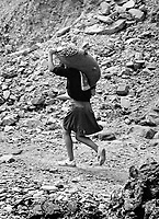 A child carries a sack of coal scavenged from the sea near Lota.