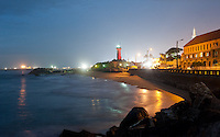Galbokka Point lighthouse in Colombo, Sri lanka lights up with red at twilight.
