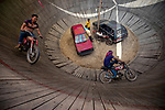 Daredevil motorcyclists ride around a steep 'wall of death' at 50 miles an hour.  The men ride the 30 ft high wall over 100 times a day for ten minutes at a time while wearing no protective gear.<br /> <br /> Dressed in t-shirts, jeans and flip flops they race around the wooden fencing performing tricks for the watching crowd.  The images were captured by professional photographer Azim Khan Ronnie in Bogra, Bangladesh.  SEE OUR COPY FOR DETAILS.<br /> <br /> Please byline: Azim Khan Ronnie/Solent News<br /> <br /> © Azim Khan Ronnie/Solent News & Photo Agency<br /> UK +44 (0) 2380 458800