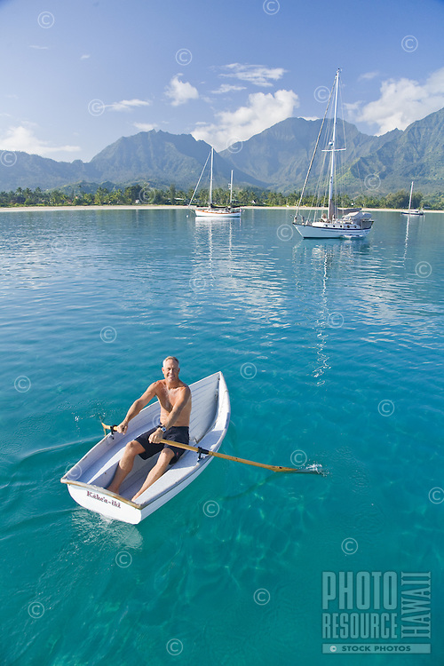 Man rowing a dinghy in Hanalei Bay with Namolokama Mountain in the background