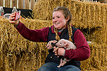 Pictured: Livestock manager Hollie Longman with two of the newly born Kunekune piglets at Longdown Activity Farm in the New Forest, Hants as she records a video for social media showcasing the new litter of piglets born this week.<br /> <br /> The farm have created a virtual experience for members called 'Longdown Little Farmers', designed to showcase the different animals on the farm through a series of individual videos for members of the public and schools who have been unable to visit the farm due to the coronavirus pandemic.<br />  <br /> Early last year the farm raised a staggering £40,000 through public donations after setting a target of £5,000 which has gone towards the upkeep of the farm during the three national lockdowns. <br /> <br /> © Jordan Pettitt/Solent News & Photo Agency<br /> UK +44 (0) 2380 458800
