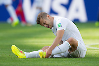 Jack Wilshere of England holds his injured ankle