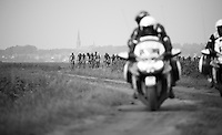 re-grouped peloton riding neutralised over one of the more serious 'gravel' (mud) sections<br /> <br /> 90th Schaal Sels 2015