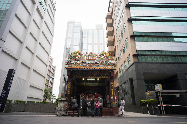 Believers worship at a mini Temple of the God of Earth in Neihu Technology Park, Taipei, Taiwan, 2015.