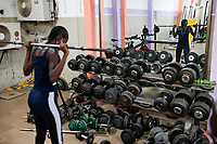 SENEGAL, Thies, gym, fitness and body building Studio, young woman doing training with weight lifting / junge Frau im Fitness Studio, Training mit Gewichte heben